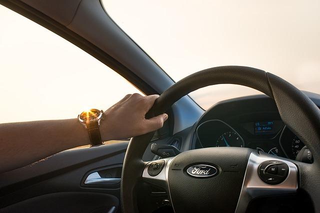 La main d'un homme sur le volant d'une voiture